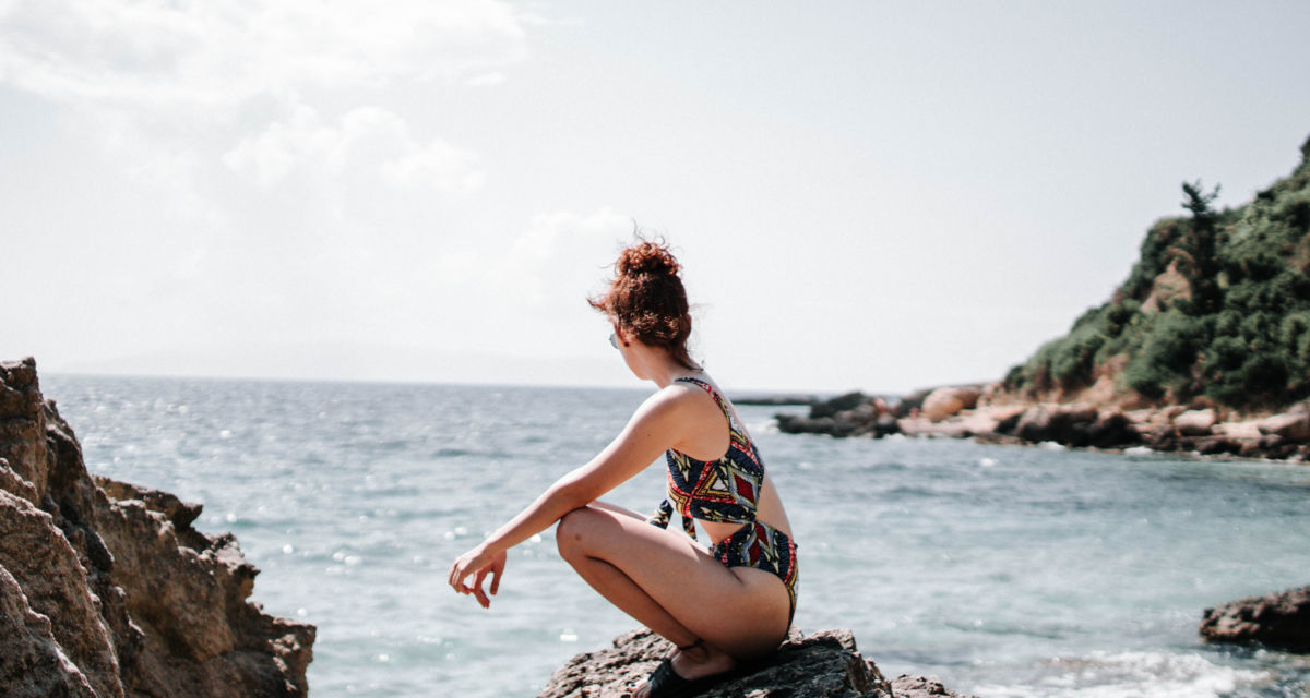 Canva Woman in Swim Suit Sitting on a Rock